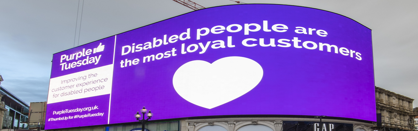 An advert in Piccadilly Circus for Purple Tuesday. Reads Disabled people are the most loyal customers