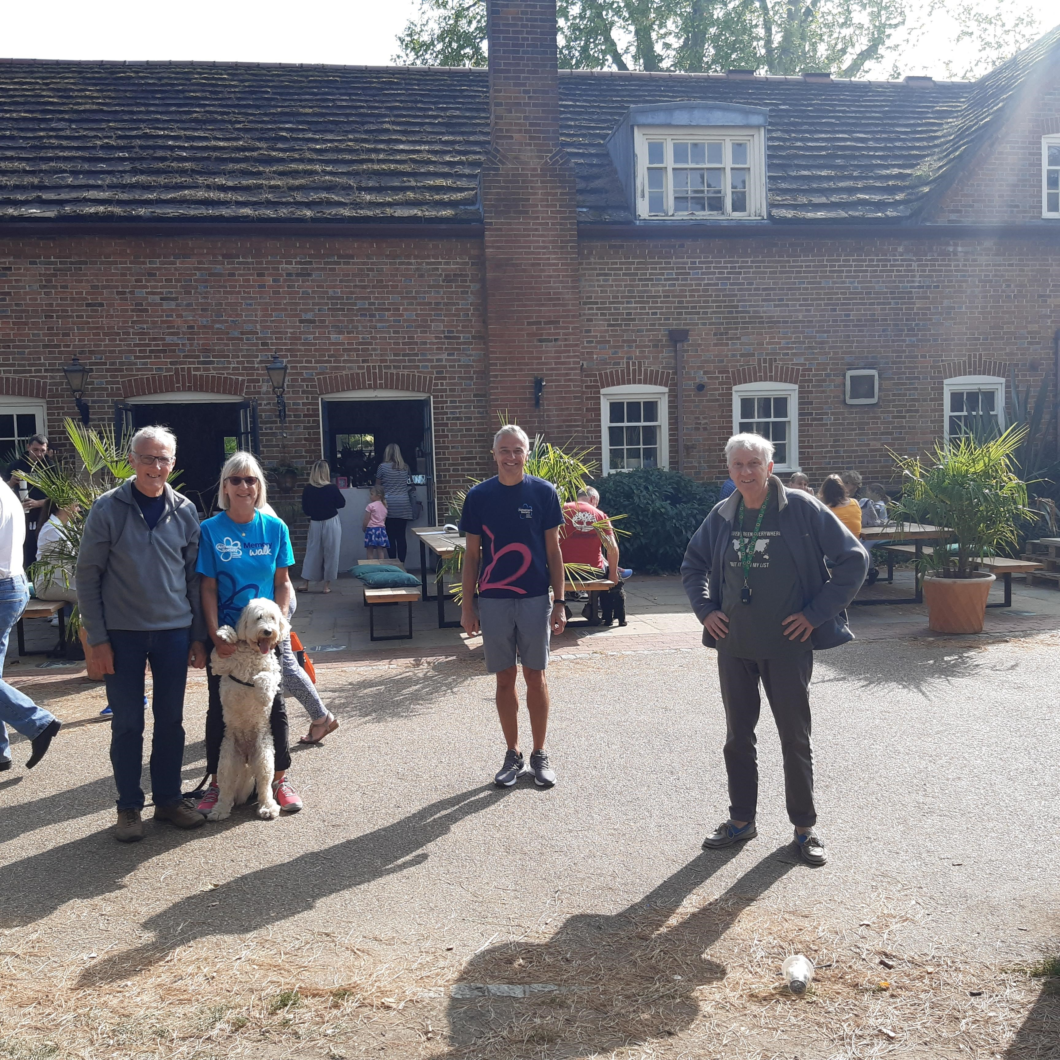 Tim stands outside a building in a courtyard flanked by two memory walkers with a dog and another man to his right.